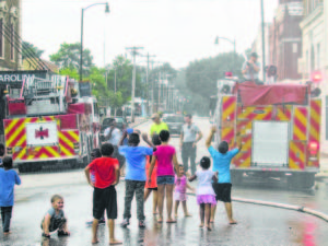 Children get doused by a Lumberton Fire Department truck during National Night Out in Lumberton on Tuesday. The annual event aims to bring police and residents together.